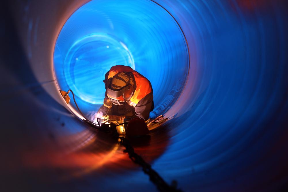Worker welding a gas pipeline