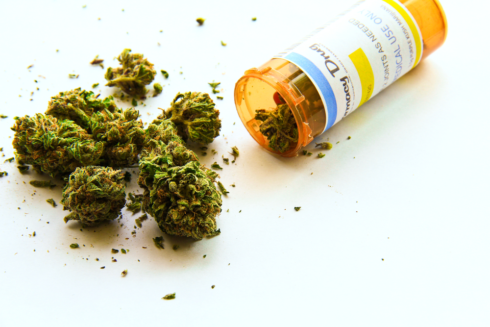 Medical marijuana in a prescription bottle spilling on flat surface
